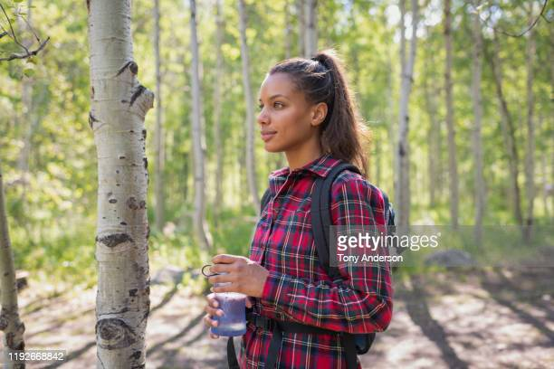 young woman holding water bottle on hiking trail - north america stock pictures, royalty-free photos & images