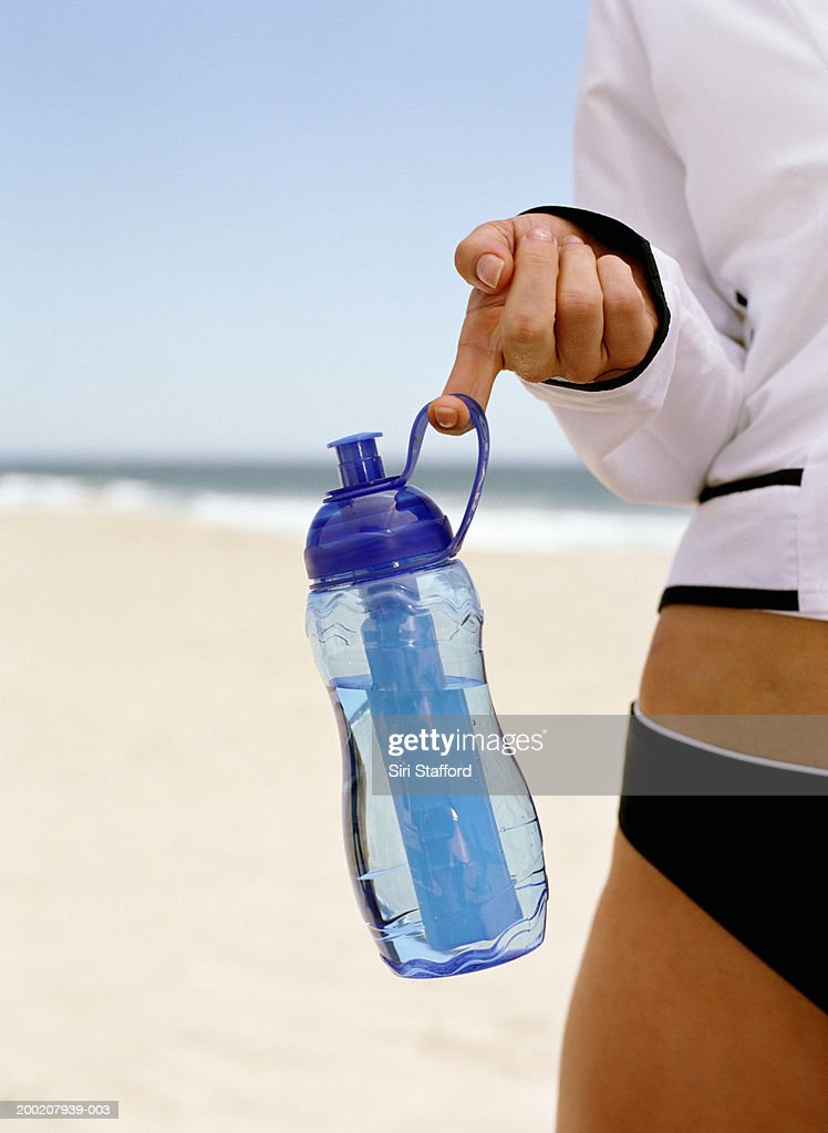 Young woman holding water bottle (mid section) : Stock Photo