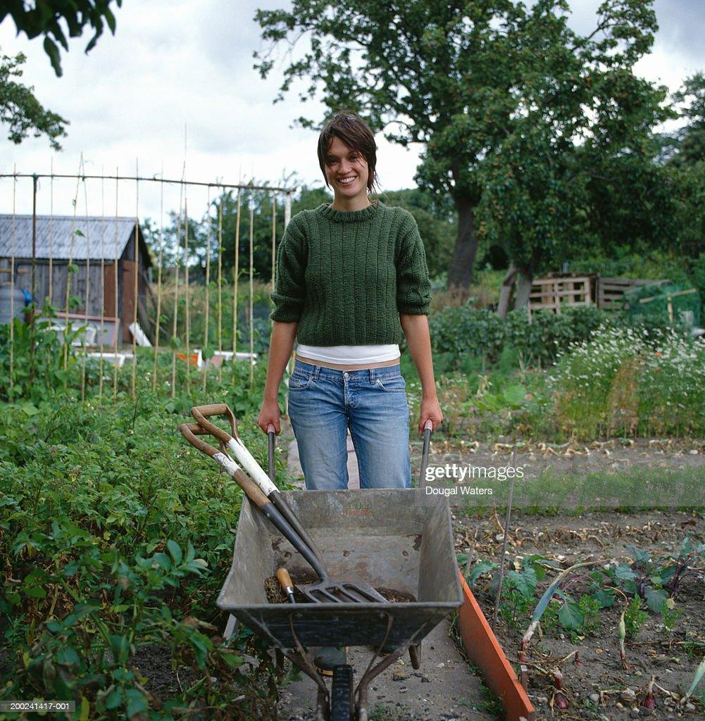 Young Woman Holding Wheelbarrow In Vegetable Garden ...