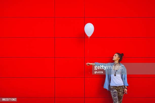 Young woman holding white balloon against the red wall