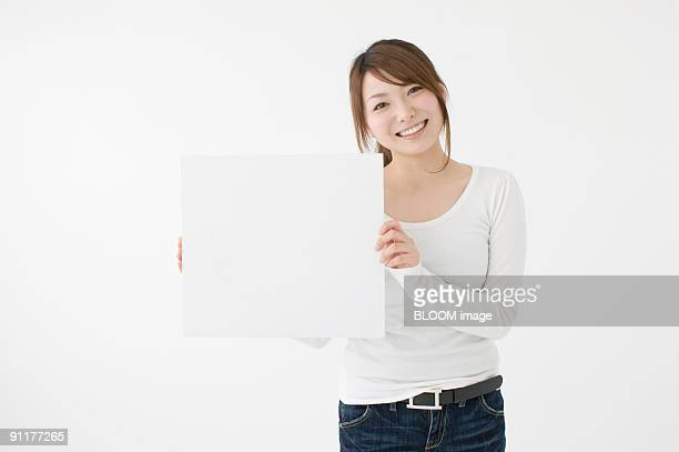Young woman holding white board, studio shot