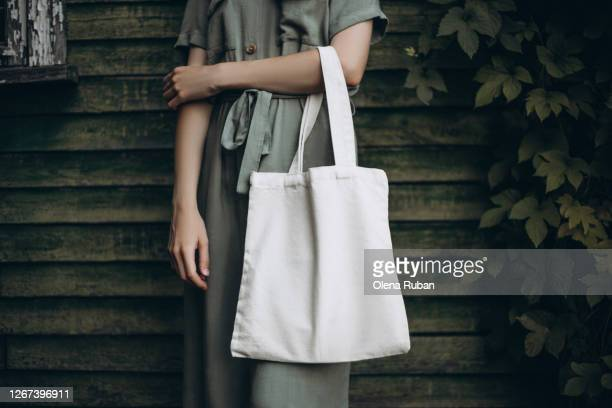 young woman holding white eco bag - reusable bag stock pictures, royalty-free photos & images