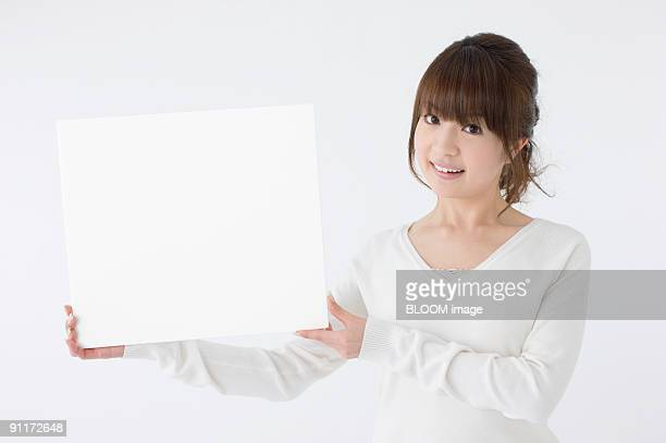 Young woman holding whiteboard