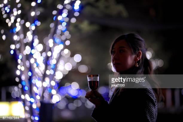 クリスマス ライトでワイングラスを保持している若い女性