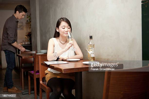 Young woman holding wine glass in restaurant