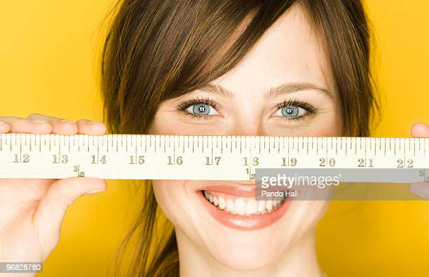 young woman holding wooden ruler in front of face - bricolage humour photos et images de collection