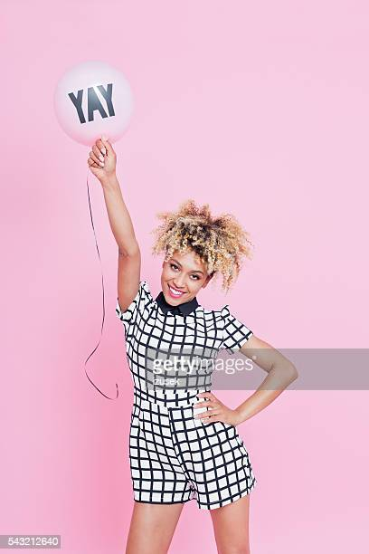 Young woman holding YAY balloon