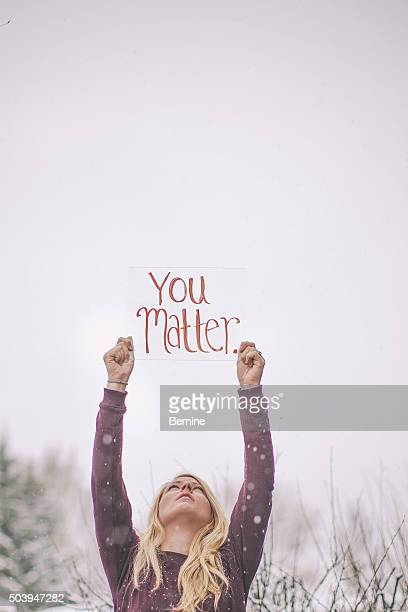 Young Woman holding You Matter sign in Snowy scene