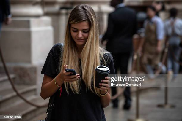 A young woman holds a coffee drink as she checks her mobile phone during the opening of Europe's largest and Italy's first Starbucks Reserve Roastery...