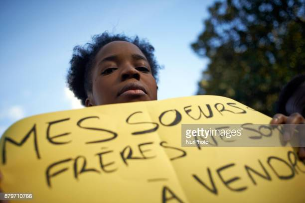 A young woman holds a placard reading 'My sisters and brothers are not on sale' Due to a report of CNN on slave trade of migrants in Libya a protest...