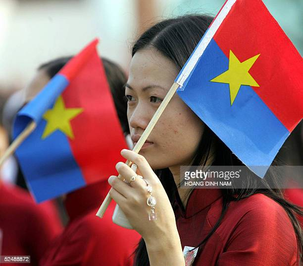 A young woman holds a Vietnamese flag during a parade 29 March 2005 in the central coastal city of Danang to mark the 30th anniversary of the...