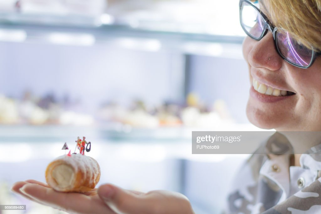 Young woman holds cannolo with miniatures in a pastry shop : Foto stock