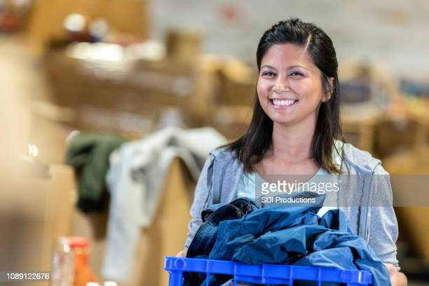 young woman holds crate of clothing at charity event - donation box stock pictures, royalty-free photos & images