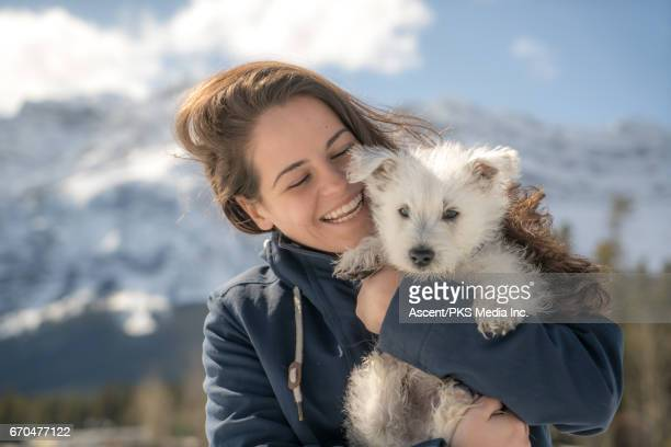 Young woman holds dog, in snowy mountain setting