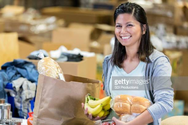 young woman holds food items as she packs bags of food - altruismo foto e immagini stock