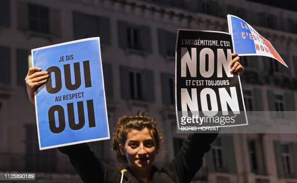 A young woman holds placards as she takes part with others in a rally against antisemitism in Marseille on February 19 2019 A flareup of antiSemitic...