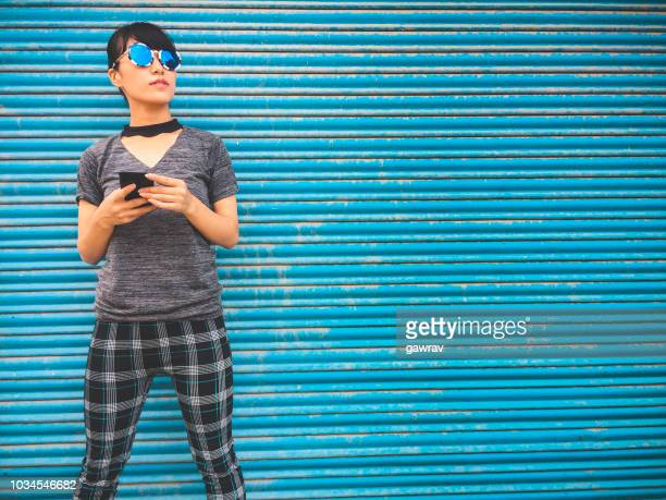 若い女性は、スマート フォンを保持し、青いシャッター背景に立っています。 - 建具 シャッター ストックフォトと画像