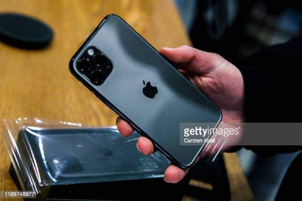 Young woman holds the new Apple iPhone 11 on the first day of the phone's sale at the Apple Store on September 20, 2019 in Berlin, Germany. The new...