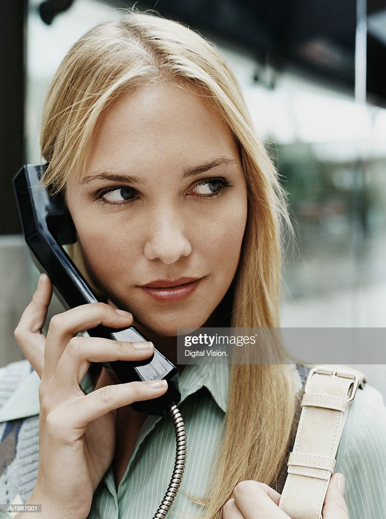Young Woman Holds the Telephone Receiver of a Payphone : Stock Photo