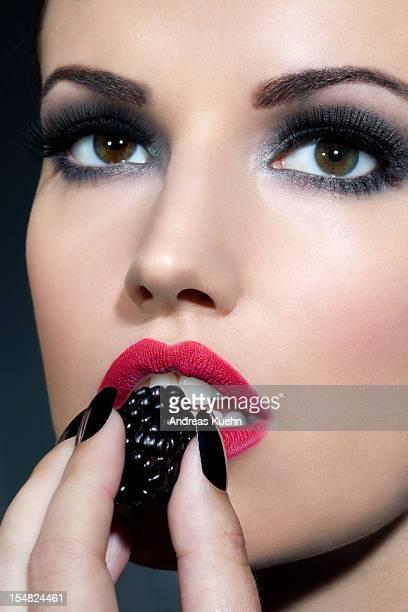 Young woman holging blackberry fruit, portrait.