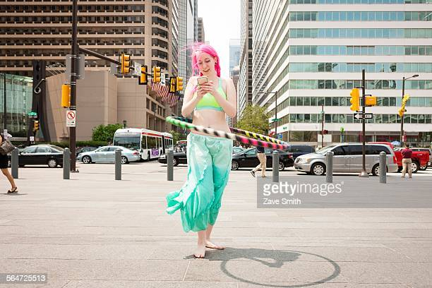 Young woman hoola hooping whilst reading smartphone text, Philadelphia, Pennsylvania, USA