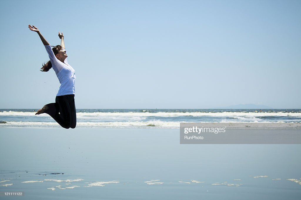 young woman hopping on the beach : Stock Photo