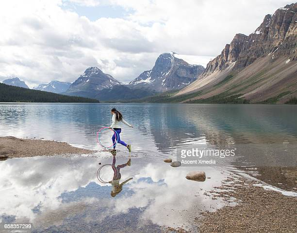 Young woman hops between rocks,hoops,mountain lake
