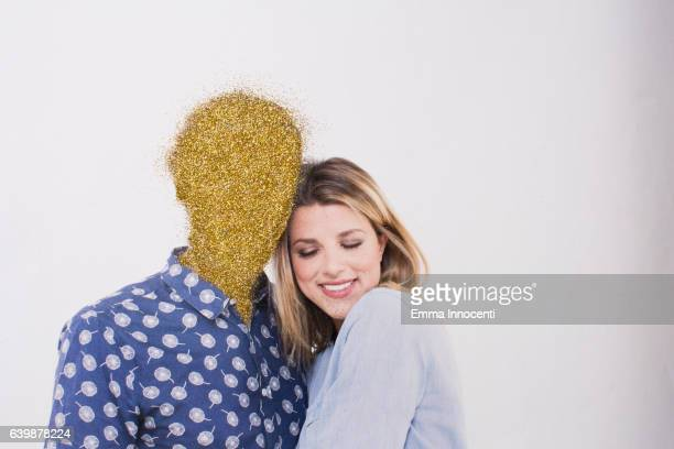 Young woman hugging a man with a golden face