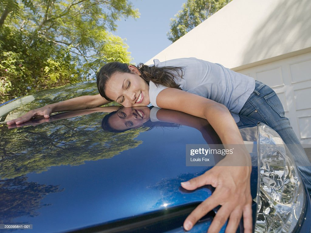Young woman hugging car, smiling, eyes closed : Stock Photo