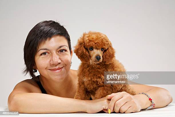 giovane donna abbracciare un cucciolo cane barboncino nano migliori amici - barboncino nano foto e immagini stock