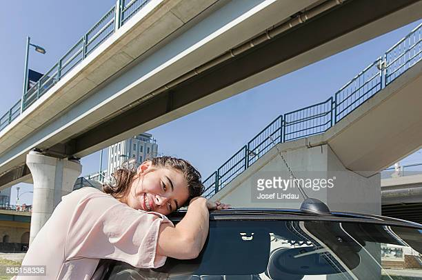 Young woman hugging her car