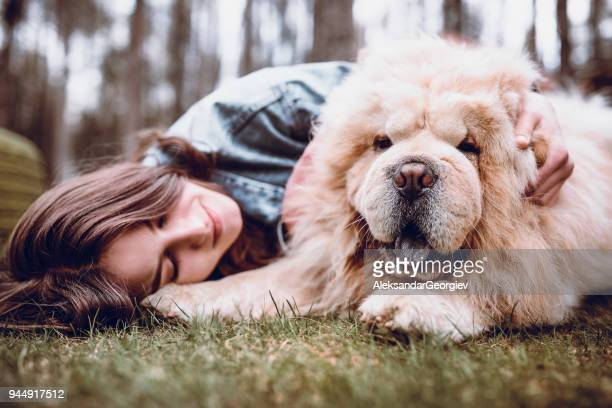 young woman hugging her chow chow dog in the park - chow dog stock pictures, royalty-free photos & images
