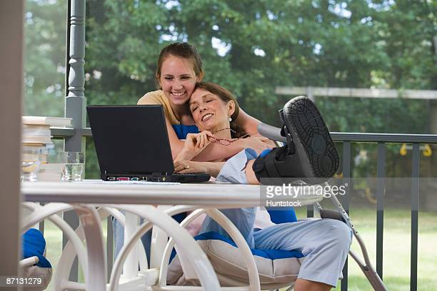 Young woman hugging her disabled mother from behind and smiling