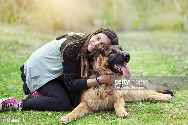 young woman hugging her german shepherd in the park - german shepherd stock pictures, royalty-free photos & images