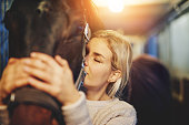 Young woman hugging her horse in stables before a ride