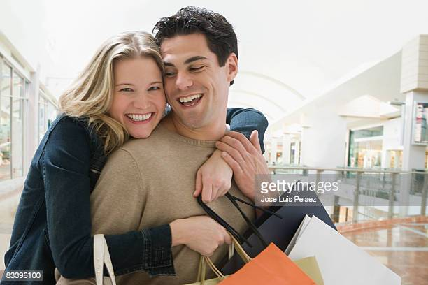 Young woman hugging husband with shopping bags