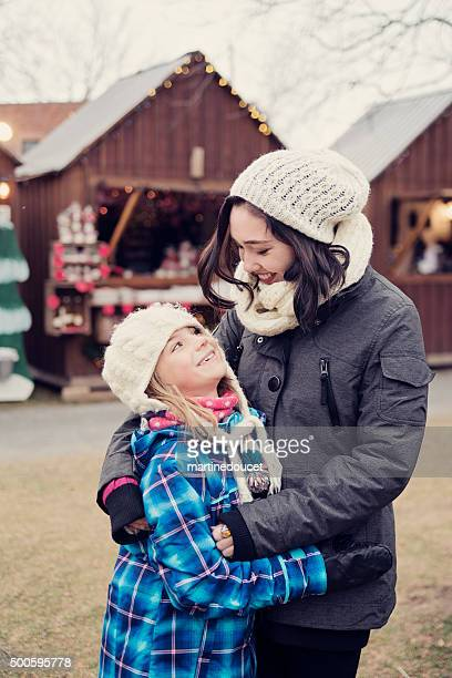 """young woman hugging little girl at an outdoors christmas market. - """"martine doucet"""" or martinedoucet stock pictures, royalty-free photos & images"""