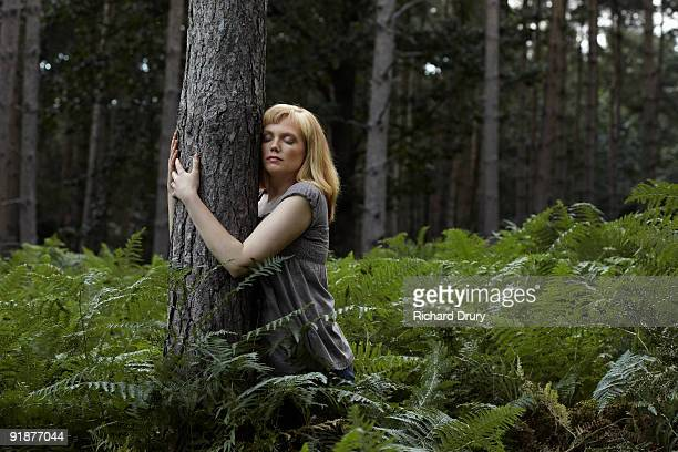 young woman hugging pine tree in forest - tree hugging stock pictures, royalty-free photos & images