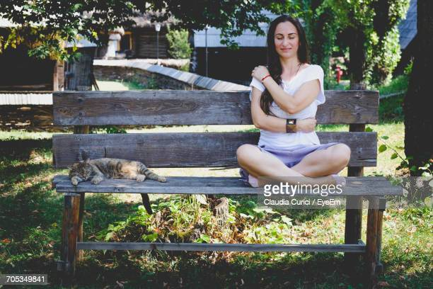 Young Woman Hugging Self By Cat On Bench At Park