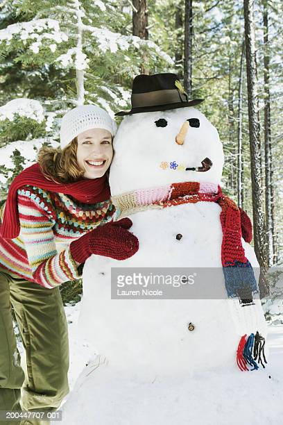 Young woman hugging snowman, smiling, portrait