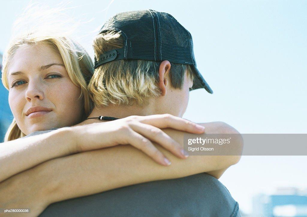 Young woman hugging teenage boy, looking at camera : Stockfoto