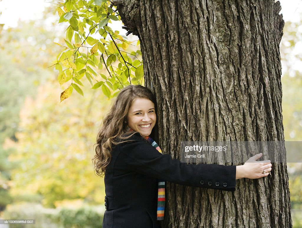 Young woman hugging tree, smiling, portrait (focus on foreground) : Stock Photo