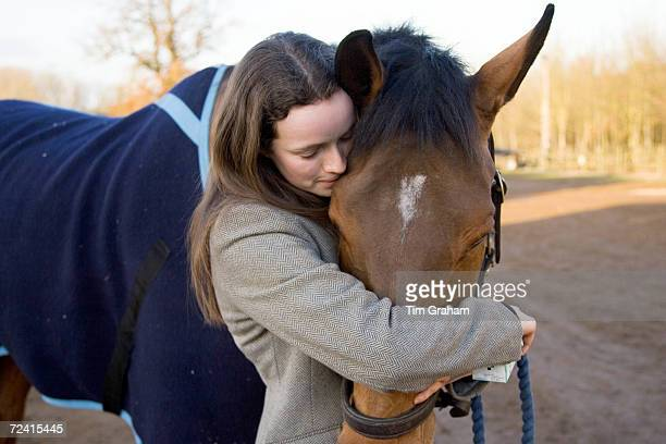 Young woman hugs Cleveland Bay cross Thoroughbred horse Oxfordshire United Kingdom