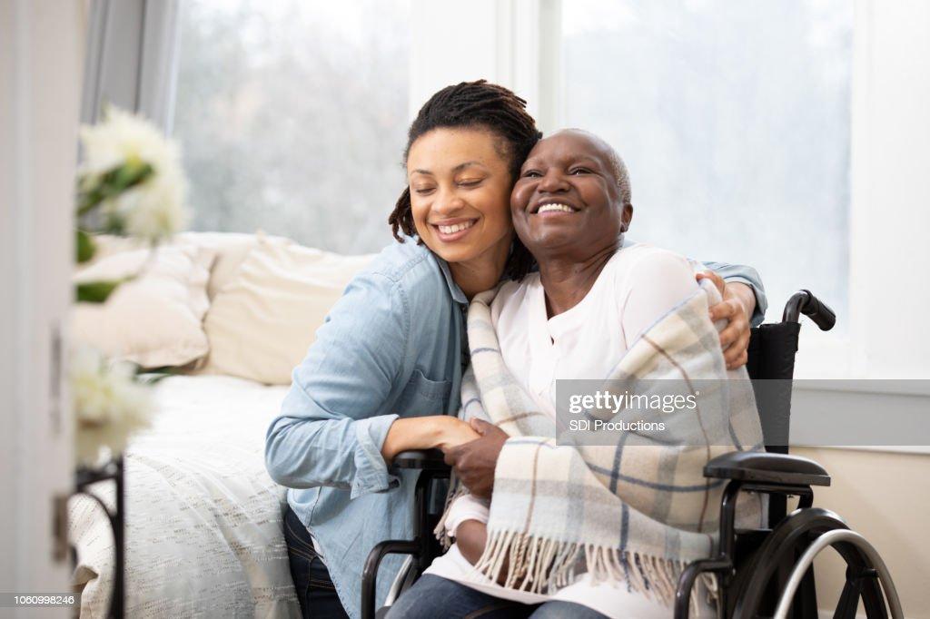 Young woman hugs senior woman in wheelchair : Stock Photo