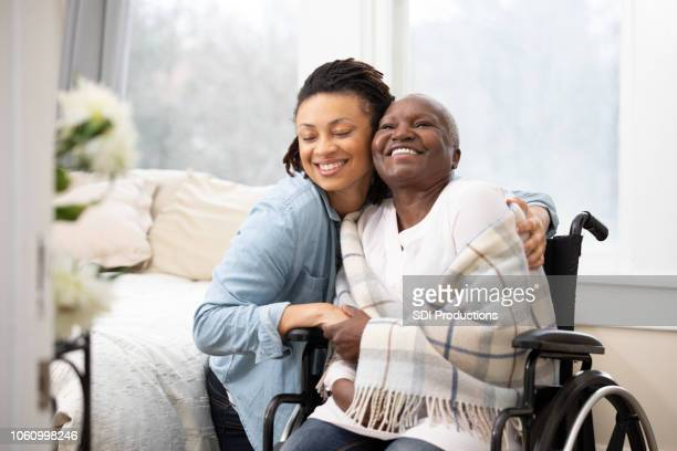 young woman hugs senior woman in wheelchair - african american family home stock photos and pictures