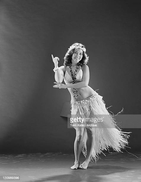 young woman hula dancer in traditional clothing dancing on black background, smiling, portrait - hula dancer stock pictures, royalty-free photos & images