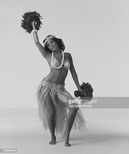Young woman hula dancer with feathered gourd rattle and dancing on white background, smiling, portrait