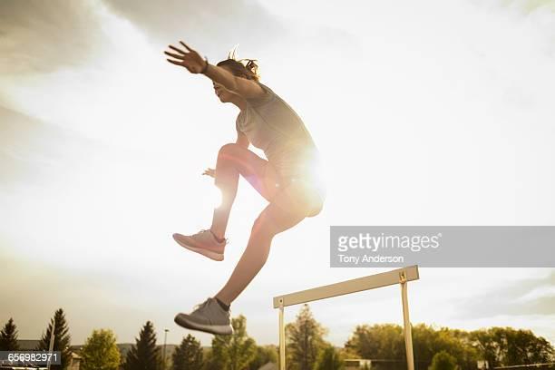 Young woman hurdler jumping