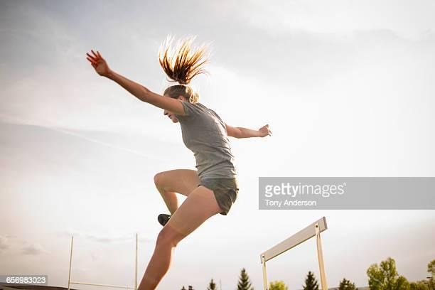 Young woman hurdler landing jump