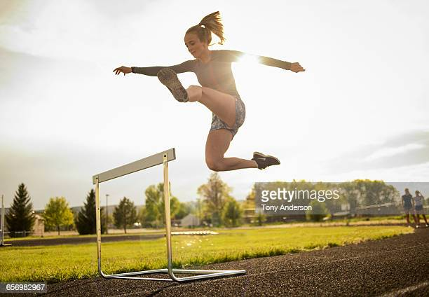 young woman hurdler on school track - extra long stock pictures, royalty-free photos & images